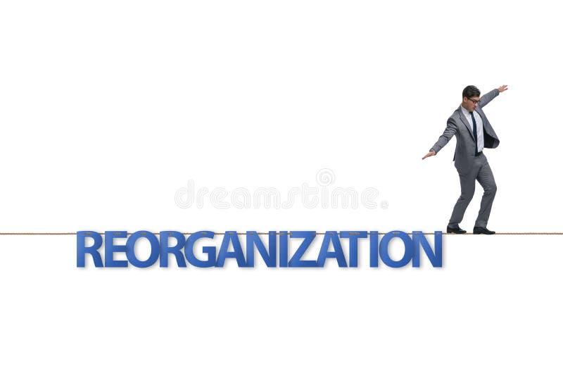 Le concept de r?organisation avec l'homme d'affaires marchant sur la corde serr photo libre de droits
