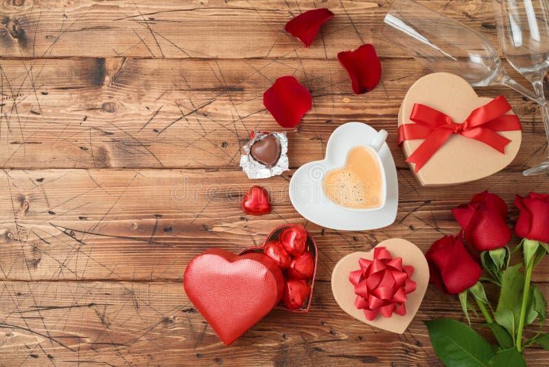 Le concept de Saint-Valentin avec la tasse de café, chocolat de forme de coeur, a monté des fleurs et des boîte-cadeau sur le fon photos libres de droits