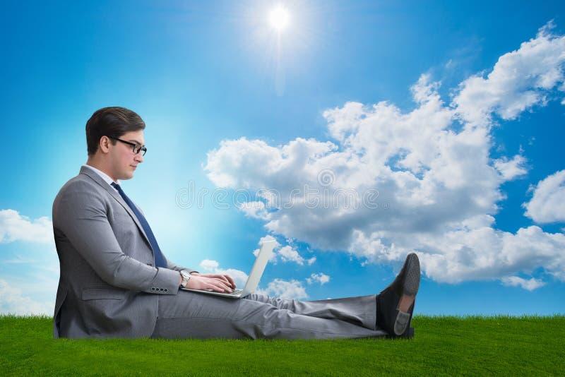 Le concept de télétravail avec l'homme d'affaires travaillant à l'herbe photos stock