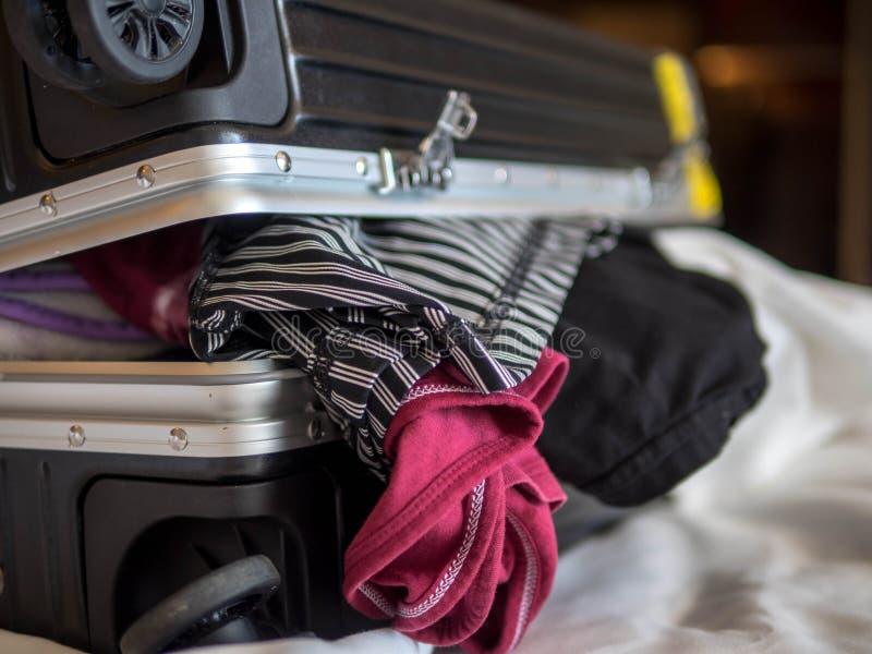 Le concept de voyage et de vacances, emballant beaucoup de vêtements et substance dans la valise sur le lit se préparent au voyag images stock