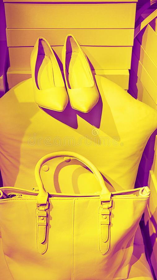 Le concept des accessoires femelles à la mode mettent en sac des chaussures sur les boîtes vides et le fond jaune images libres de droits