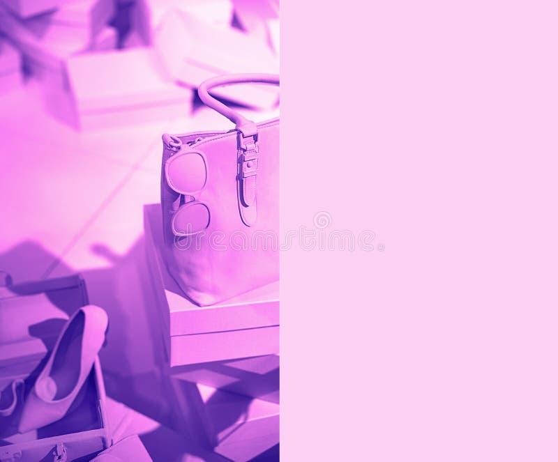 Le concept des accessoires femelles à la mode mettent en sac des verres de chaussures sur les boîtes et le fond au néon vif de co photographie stock