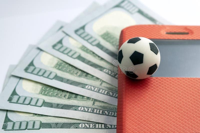 Le concept des sports pariant avec un smartphone Une boule de souvenir du football sur le coin d'un écran de téléphone portable d images stock