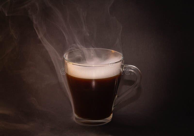 Le concept du café vraiment chaud avec de la crème sur un fond d'isolement foncé photo libre de droits
