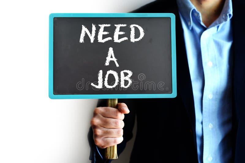 """Le concept du chômage avec le jeune homme tenant un conseil avec """"need un message de  de job†photographie stock libre de droits"""