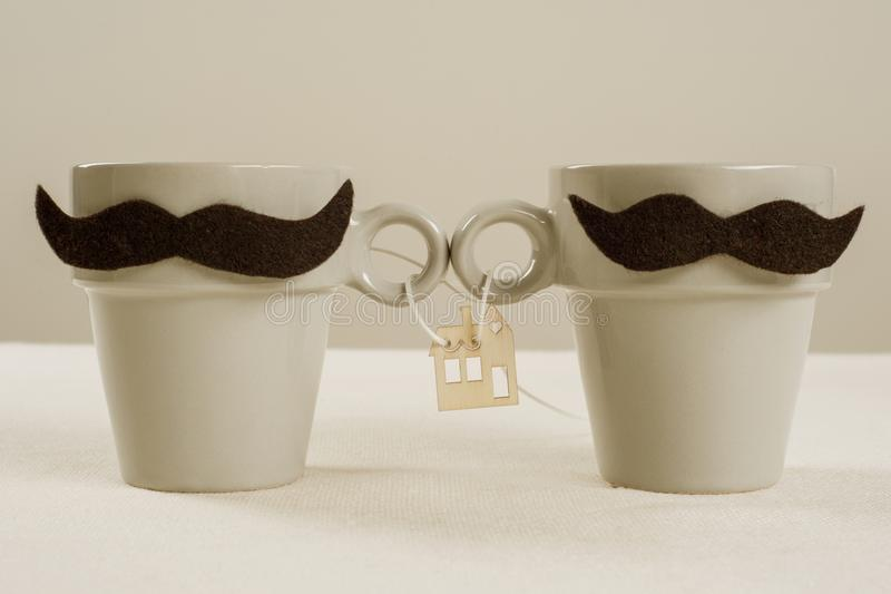 Le concept du logement commun, nouvelle maison, une famille Couples homosexuels de tasses symboliques, image en bois d'une maison photo stock