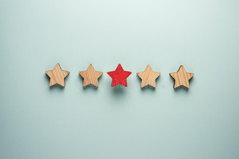 Le concept du retour de cinq étoiles Une étoile rouge en plus de l'ordinaire quatre ceux photographie stock
