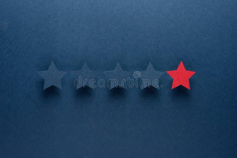 Le concept du retour ou de l'excellence est différent de chacun, soit le premier l'étoile rouge se tient contre le bleu photographie stock libre de droits