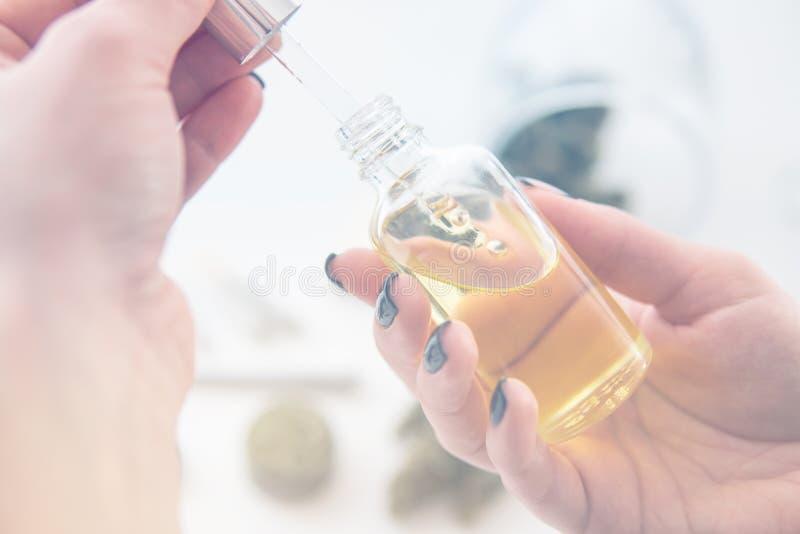 Le concept médical de chanvre, extrait de marijuana sur le fond blanc, le cannabis CBD d'huile dans des femmes de pipette remett photos stock
