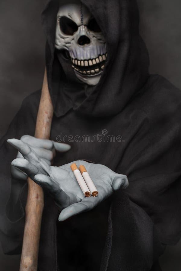 Le concept : mises à mort de tabagisme Ange de la mort tenant la cigarette photographie stock