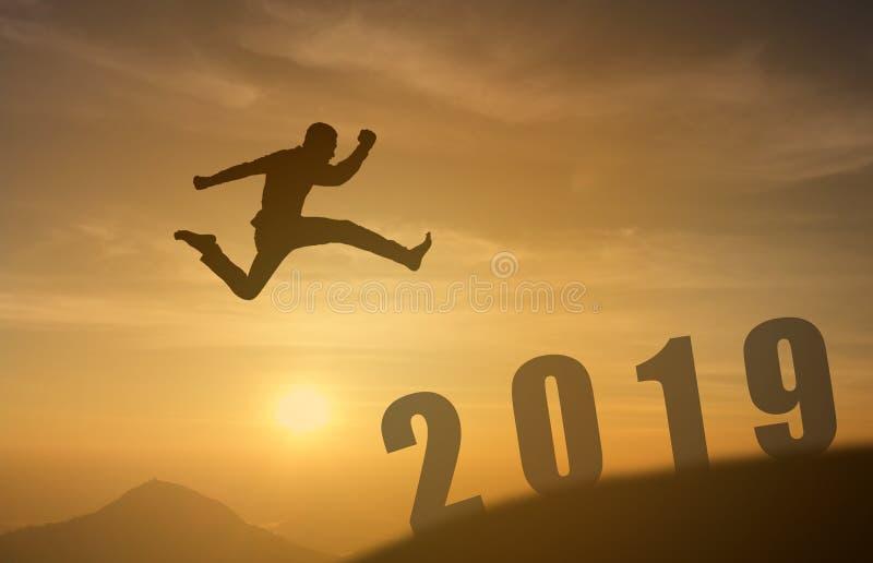 le concept réussi de l'homme 2019 courageux, homme de silhouette sautant par-dessus le soleil entre l'espace de la montagne à 201 image libre de droits