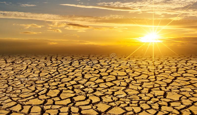 Le concept worming global d'argile de sol de désert aride de Sun a fendu le coucher du soleil dramatique roussi de paysage de dés photographie stock libre de droits
