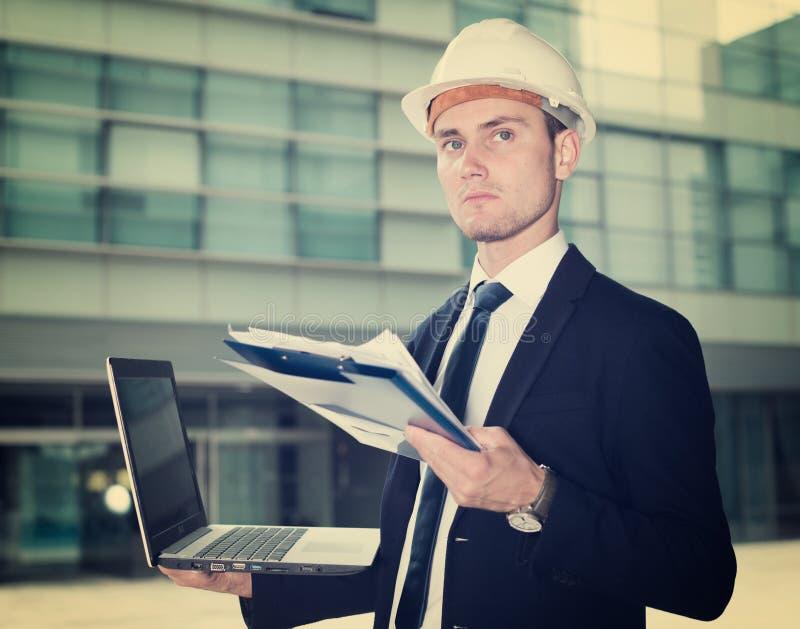 Le concepteur dans le costume et le chapeau avec le dossier examine les documents W images libres de droits