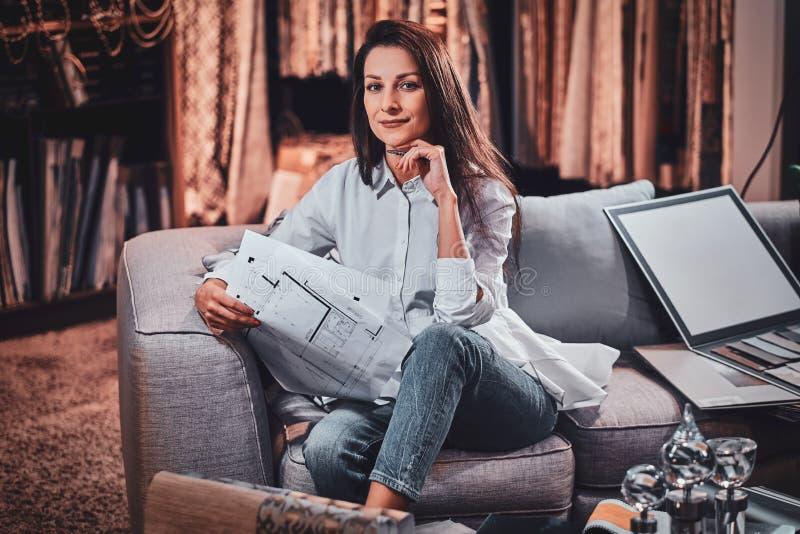 Le concepteur gai s'assied sur le sofa à son propre studio de vêtement photos stock