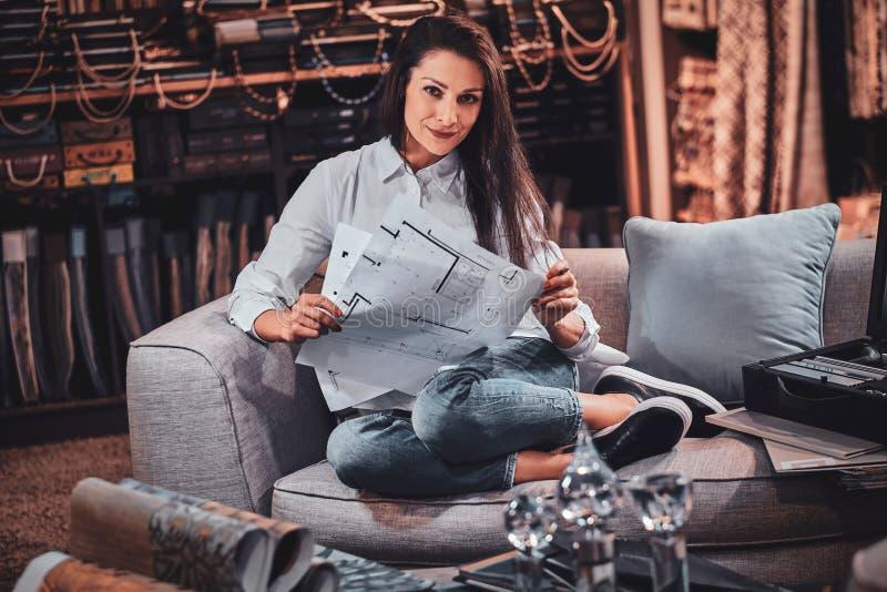 Le concepteur gai s'assied sur le sofa à son propre studio de vêtement image stock