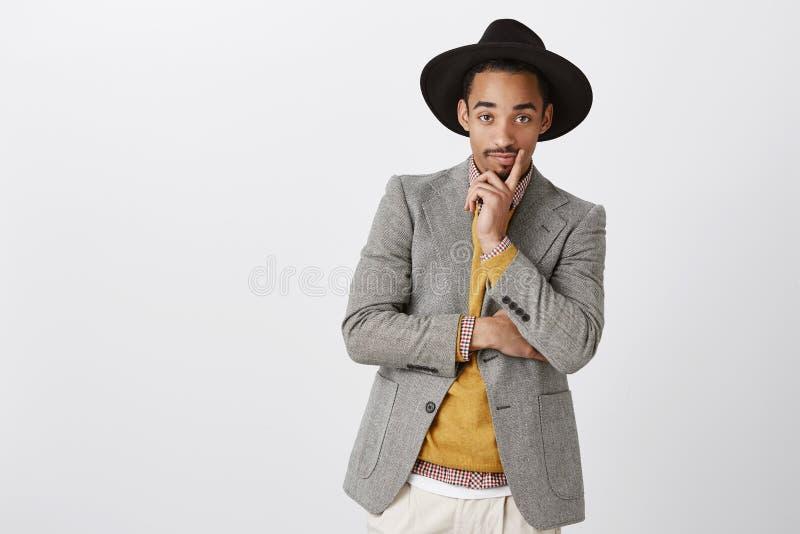 Le concepteur regarde le modèle dans des ses vêtements Portrait de jeune homme beau chic dans l'équipement et le chapeau formels  image libre de droits