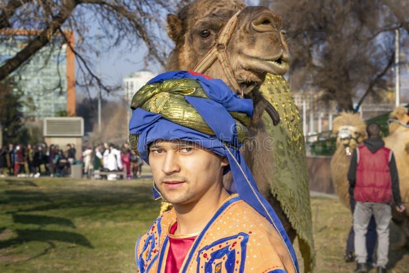 Le conducteur de chameau portant les vêtements nationaux traditionnels mène un chameau le long d'une rue de ville pendant des vac photo stock