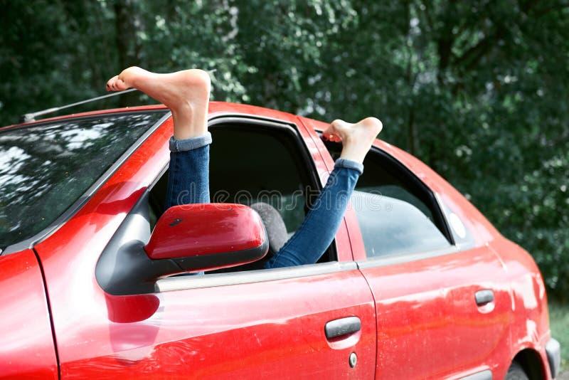 Le conducteur de jeune femme se reposant dans une voiture rouge, a mis ses pieds sur la fenêtre de voiture, concept heureux de vo image libre de droits