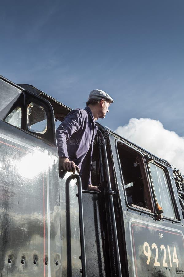 Le conducteur de train de vapeur regarde hors de sa carlingue image libre de droits