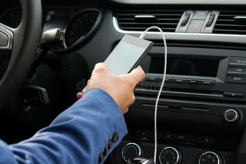 Le conducteur du véhicule, prises dans le sien remettent le téléphone relié par un fil blanc, au système de musique de voitures photos stock