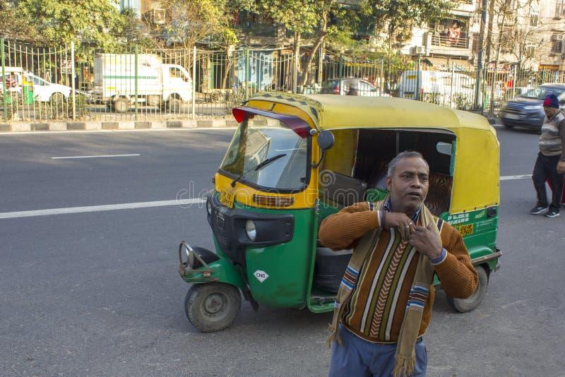 Le conducteur indien de pousse-pousse prend l'argent contre le contexte d'un taxi et d'une circulation urbaine vert-jaunes images stock