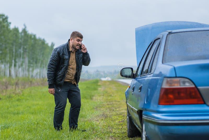 Le conducteur nerveux appelle au service SVP par le téléphone photos libres de droits