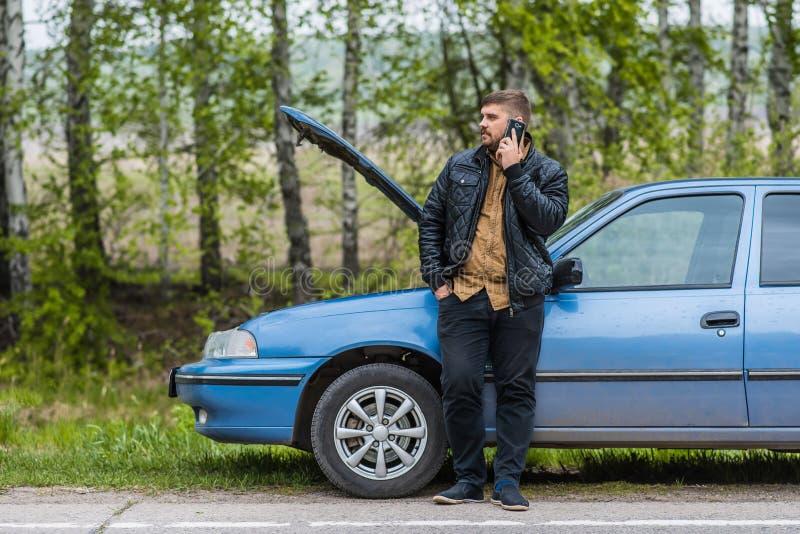 Le conducteur nerveux appelle au service SVP par le téléphone images libres de droits