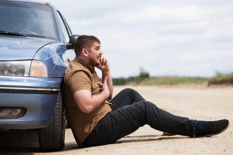 Le conducteur nerveux appelle au service SVP par le téléphone photographie stock libre de droits