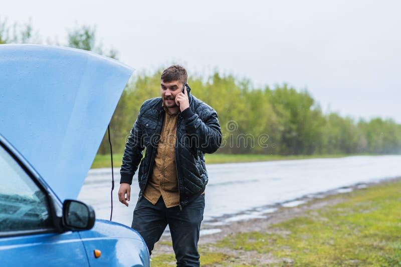 Le conducteur nerveux appelle au service SVP par le téléphone photographie stock
