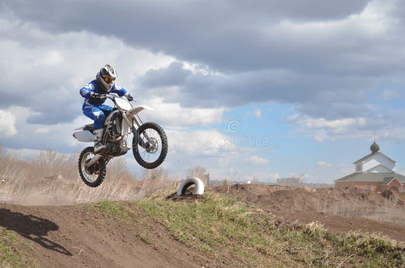 Le conducteur se tenant sur la moto de MX vole au-dessus du photographie stock libre de droits