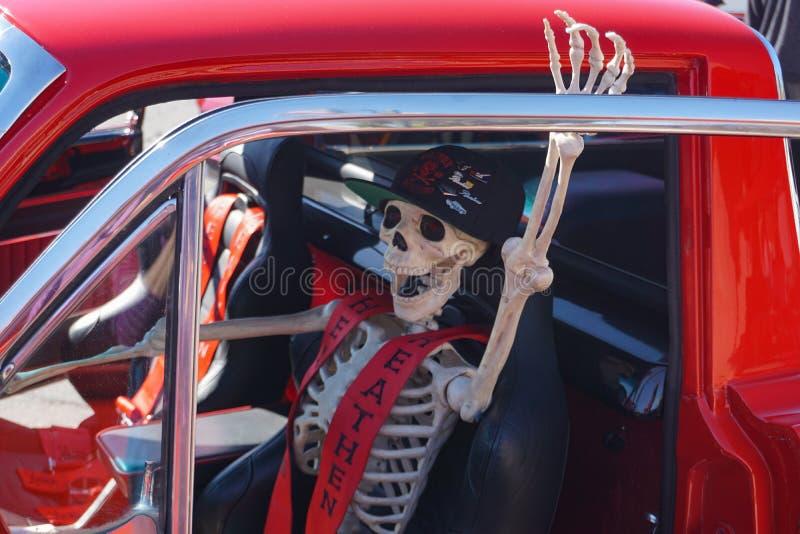 Le conducteur squelettique dans la voiture fraîche invite des cavaliers de Halloween photo libre de droits