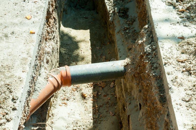 Le conduit d'égout de deux PVC s'est relié sous terre dans le fossé sur la rue photographie stock