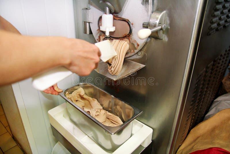 Le confiseur dans l'uniforme de chef travaille à la machine de fabricant de crème glacée  La femme produit la crème glacée des sa images stock