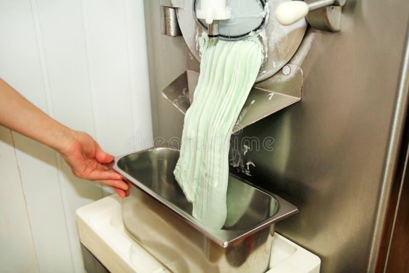 Le confiseur féminin dans l'uniforme de chef travaille à la machine de fabricant de crème glacée  Production des saveurs en bon é image stock