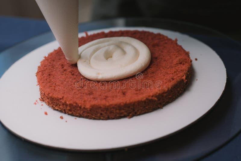Le confiseur presse la crème sur le gâteau Fille faisant un gâteau photographie stock