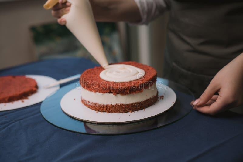 Le confiseur presse la crème sur le gâteau Fille faisant un gâteau photo libre de droits