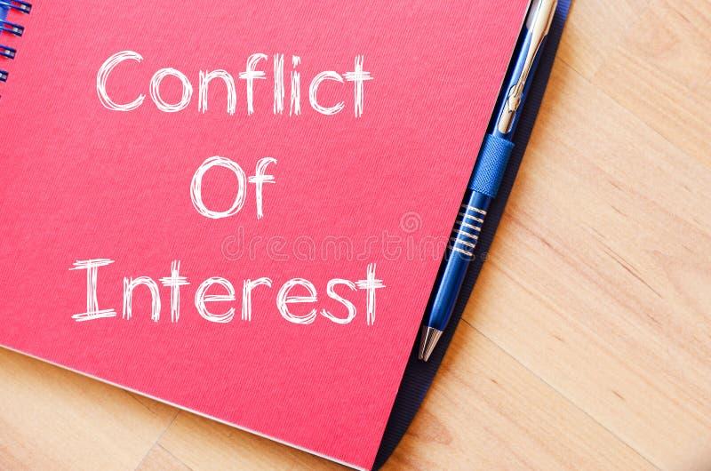 Le conflit d'intérêt écrivent sur le carnet images libres de droits
