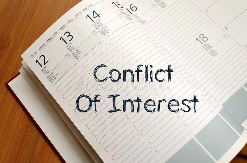 Le conflit d'intérêt écrivent sur le carnet images stock