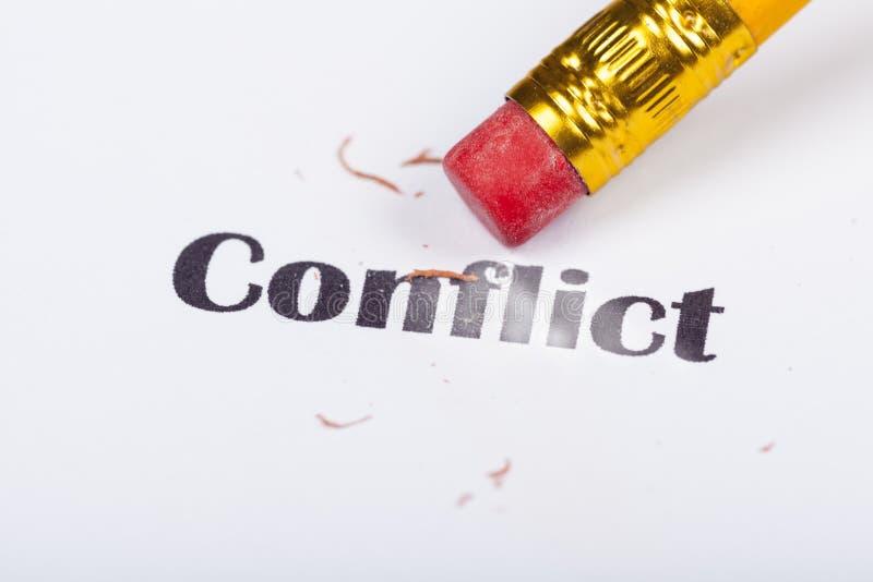 Le conflit Word est effacé par un effacement de crayon - fin photographie stock libre de droits