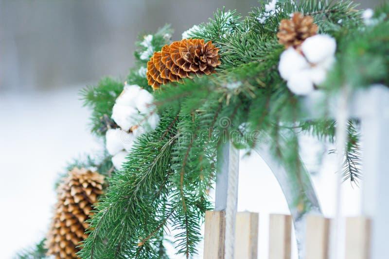 Le conifère et le gossypium de Noël tressent accrocher sur le traîneau en bois dehors images libres de droits