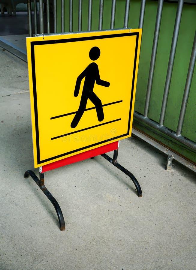 Le conseil jaune et le métal noir se tiennent avec le symb de passage pour piétons images libres de droits