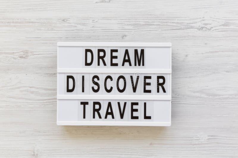 Le conseil moderne avec le rêve de ` des textes découvrent le mot de ` de voyage au-dessus du fond en bois blanc, vue supérieure  photographie stock