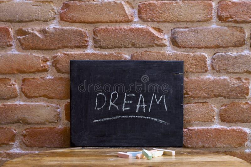 Le conseil noir avec le mot RÊVE se noient à la main sur la table en bois sur le fond de mur de briques photos libres de droits