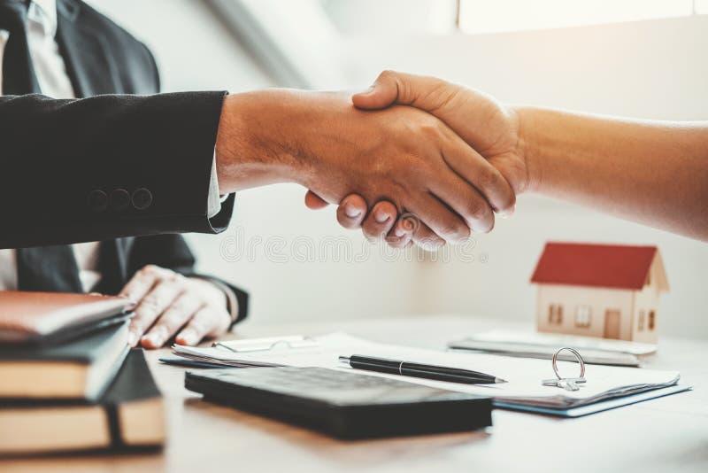 Le consignataire et accord de la poign?e de main et du signe de client se contractent, le concept ? la maison d'assurance photos stock