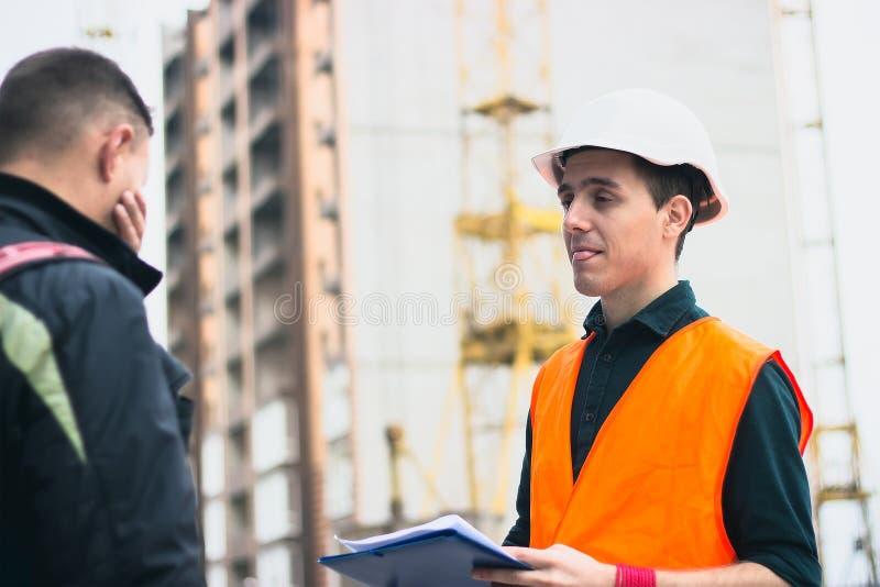 Le constructeur dans le casque montrant la langue tient des documents sur le bâtiment photos libres de droits
