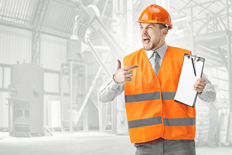 Le constructeur dans le casque orange sur le fond industriel images libres de droits