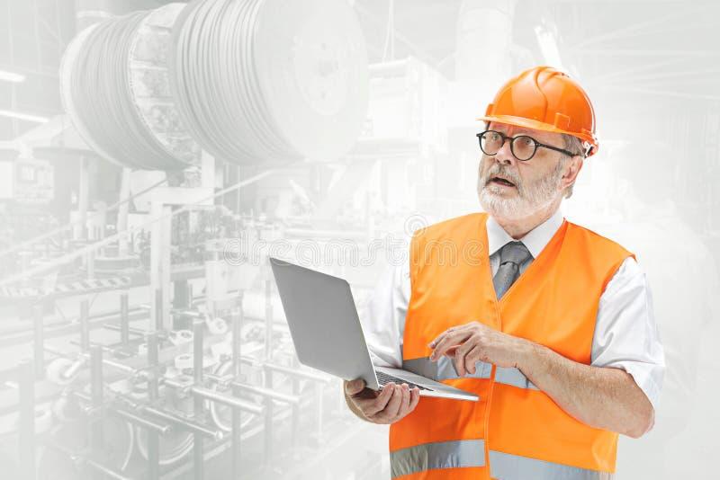 Le constructeur dans le casque orange sur le fond industriel photo stock