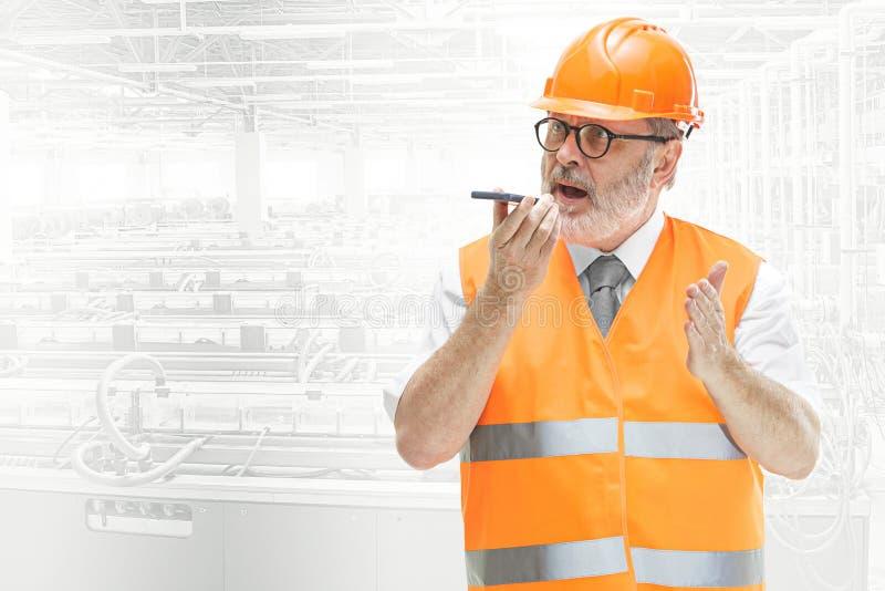Le constructeur dans le casque orange sur le fond industriel image libre de droits