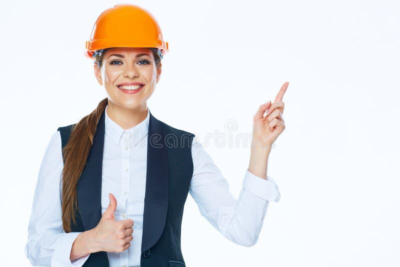 Le constructeur de femme dans le casque dirige le doigt à l'espace de copie sur le Ba blanc image stock