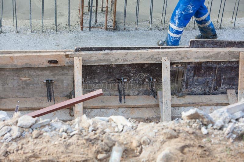 Le constructeur sur l'uniforme de port de casque de chantier de construction fonctionne images stock